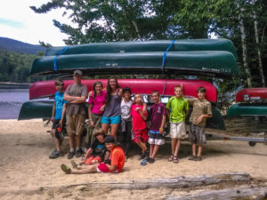 Summer camp lids in front of canoes before trip